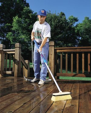 Cleaning a deck with a stiff flow-thru bush.