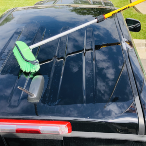 Pro-pole with a soft green brush washing a truck.