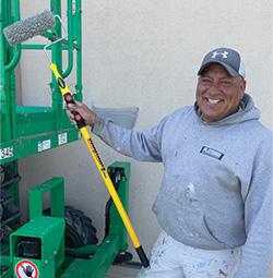 Painter holding up a Smart-Lok 3-6 ft extension pole.