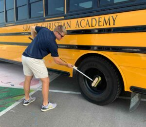 Truck 'n Bus extension pole cleaning the wheels on a school bus.